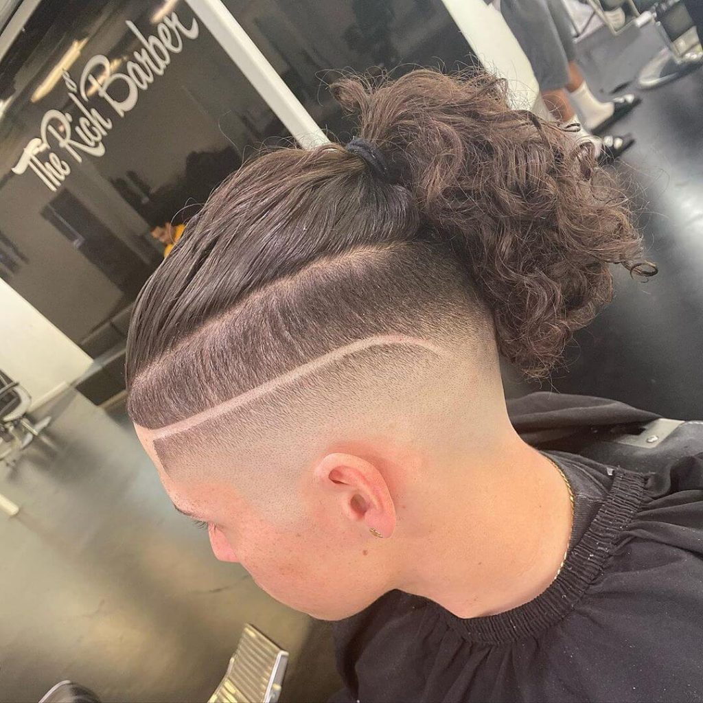 boy with short on sides long on top haircut and tail