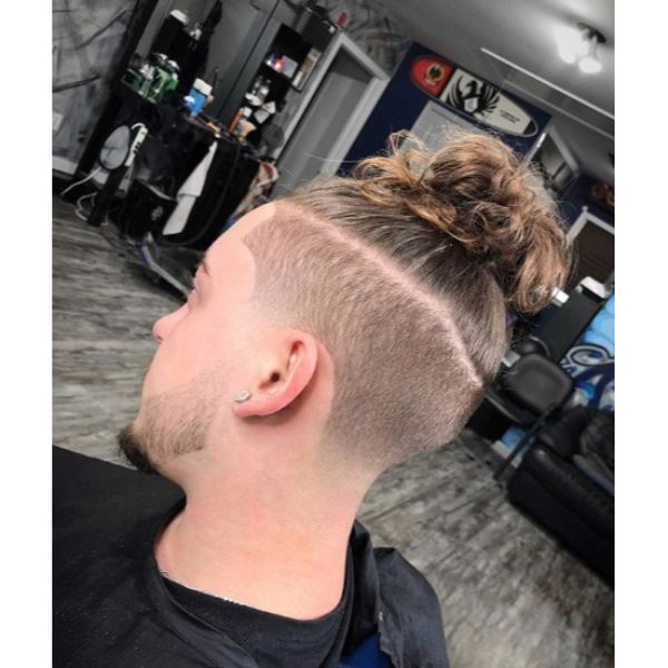 High Fade with Top Knot and Razor Design Short Sides Long Top Hairstyles