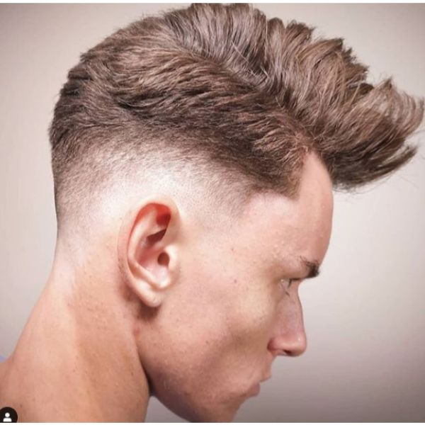 Mid Fade with Undone Pomp Short On Sides Long on Top Hairstyle