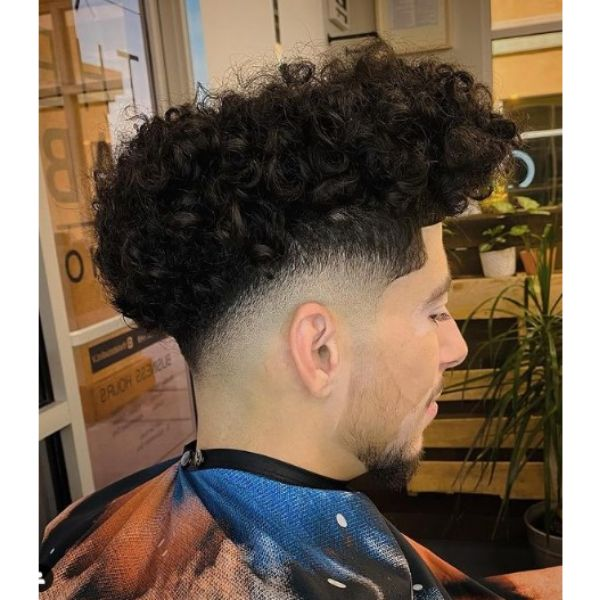 Tight Fade with Curly Top Hairstyle curly hairstyles for men