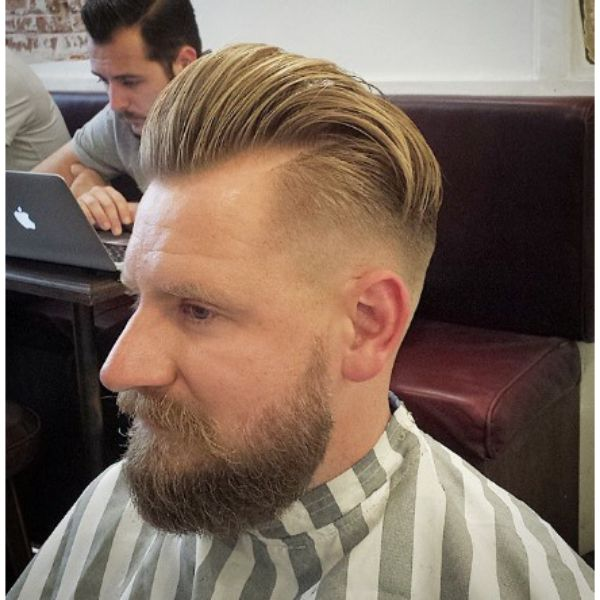 Low Fade With Blonde Slick Back Top And Beard Men Hairstyle